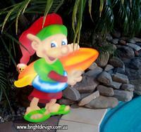 4- E-30 CG Surfboard Elf Outdoor Christmas Cut Out in a Home Garden Christmas Display