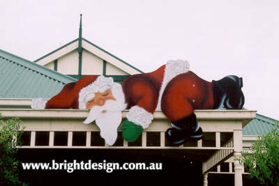 Lazy Santa Outside Christmas Cut Out in Foreground of Home Christmas Display Custom Airbrushed by Bright Design Airbrushing Studio